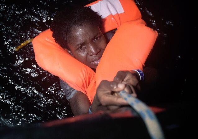 فتاة تمسك بالحبل خلال عملية إنقاذ المهاجرين قبالة السواحل الليبية، 12 أكتوبر/ تشرين الأول 2016