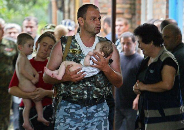 جندي من وحدة القوات الخاصة الروسي يحمل طفلاً، كان رهينة بمدرسة في بيسلان، أوسيتيا الشمالية
