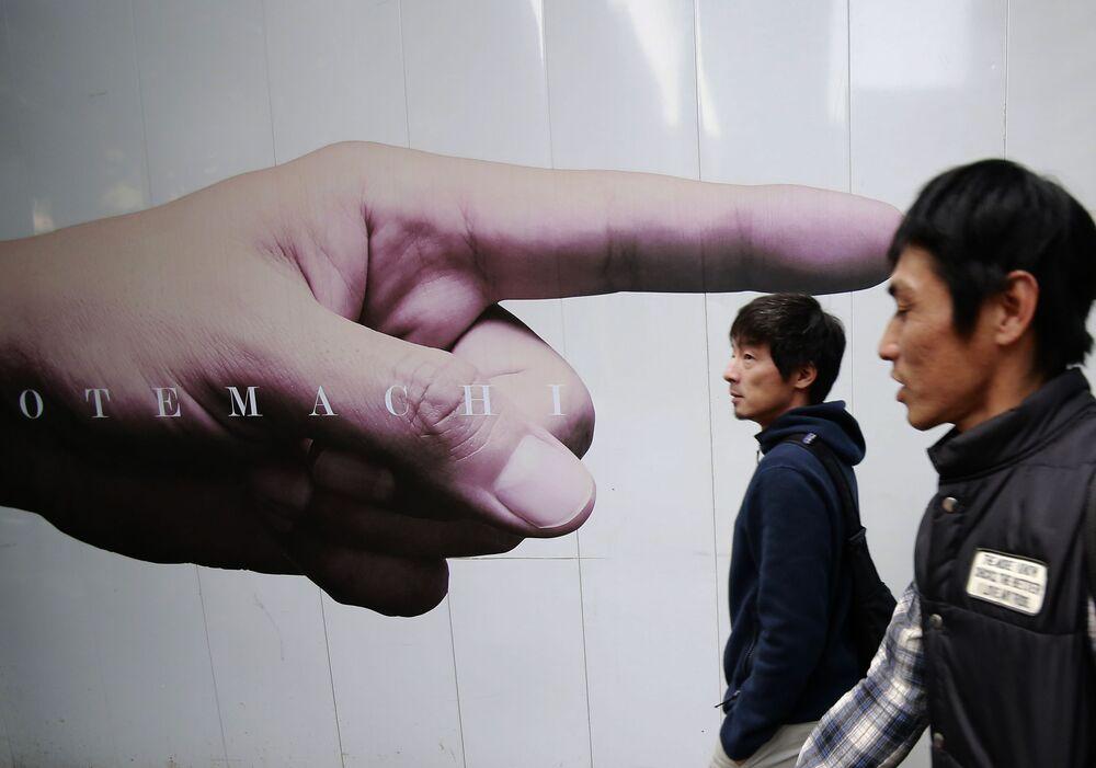 مارة يسيرون من أمام إعلان على أحد جدران مبنى في ضاحية اقتصادية يابانية، 7 نوفمبر/ تشرين الثاني 2016