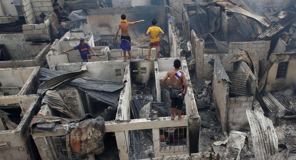 سكان حي أديشين هيلز في ماندالويونغ، يقفون فوق ركام المنازل التي تعرضت لحريق كبير، الفلبين 14 نوفمبر/ تشرين الثاني 2016