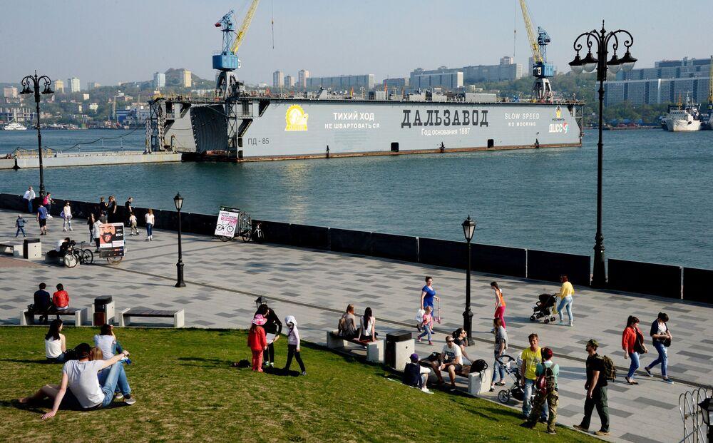 أشخاص يصطافون على شاطئ القيصر نيقولاي، أحد الشواطئ الحديثة في فلاديفوستوك، التي تم افتتاحها في الذكرى الـ 125 لتأسيس مصنع دالزافود وهو أقدم المصانع في المدينة