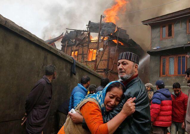 رجل يهدئ قريبته التي تبكي إثر حريق اشتعل في منزلها في سريناجار، الهند 21 نوفمبر/ تشرين الثاني 2016