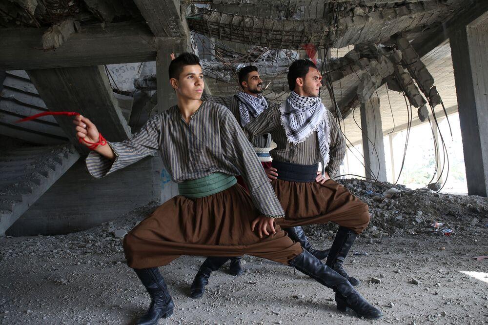 شبان من فرقة النشامة يؤدون رقص الدبكة داخل مبنى دُمّر في الحرب الأخيرة على قطاع غزة، 7 ديسمبر/ كانون الأول 2016