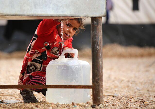 طفلة عراقية لاجئة من مدينة الموصل، تحمل وعاء لتعبئته بمياه الشرب، مخيم للاجئين بالحسكة، سوريا 5 ديسمبر/ كانون الأول 2016