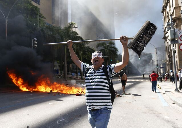 رجل يمسك رجل مكنسة خلال الاحتجاجت ضد تدابير التقشف التي تجري مناقشتها في حكومة ريو دي جانيرو، البرازيل 6 ديسمبر/ كانون الأول 2016