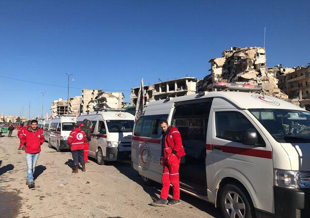 أعضاء الصليب الأحمر والهلال الأحمر في انتظار مغادرة المجموعة الأخيرة من الحافلات الخضراء لمدينة حلب الشرقية، 15 ديسمبر/ كانون الأول 2016