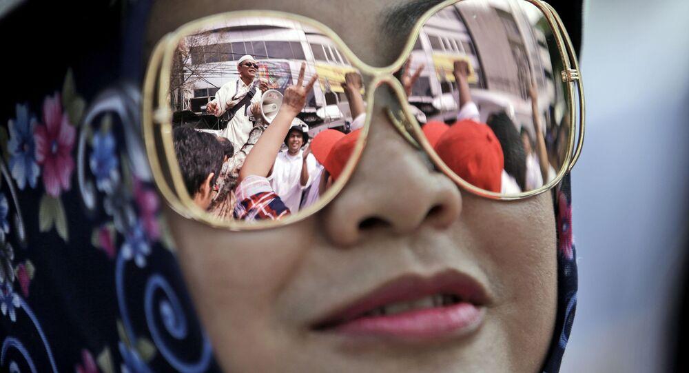 حشد من المتظاهرين أمام محكمة بشمال جاكرتا تنعكس في نظارة شمسية لامرأة، اندونيسيا 13 ديسمبر/ كانون الأول 2016