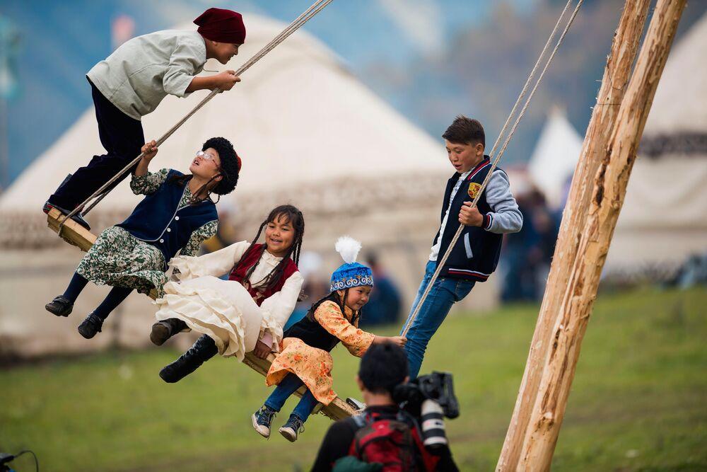أطفال يلعبون على المراجيح بمقاطعة كرغيزستان