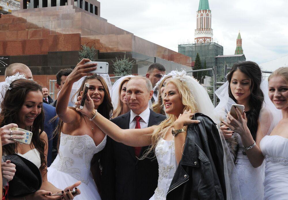 الفتيات تلتقطن صورة جماعية مع الرئيس فلاديمير بوتين خلال افتتاح مراسم عيد المدينة (موسكو) على الساحة الحمراء