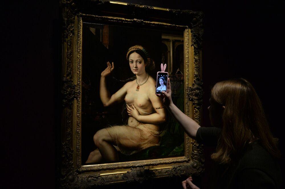 زائرة تلتقط صورة للوحة فنان إيطالي جولي رومانو تسمى سيدة خلف الحمام من المتحف البريسي دي أورسيه ، وذلك خلال معرض أولمبيا في متحف بوشكين الحكومي بموسكو