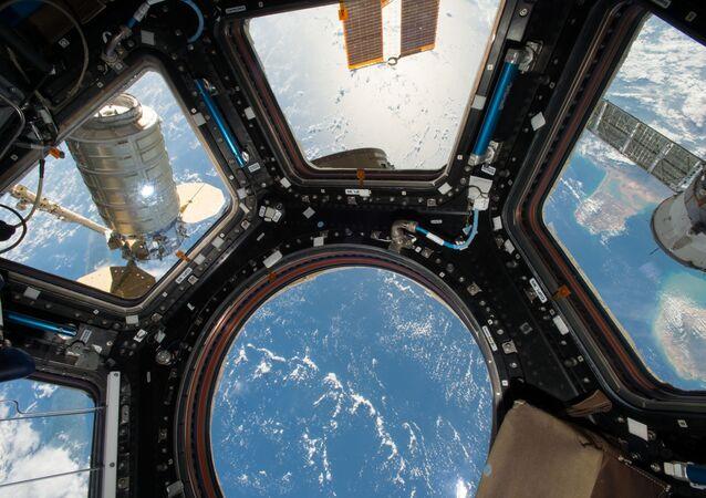 المركبة الفضائية سيغنوس عبر نافذة محطة الفضاء الدولية