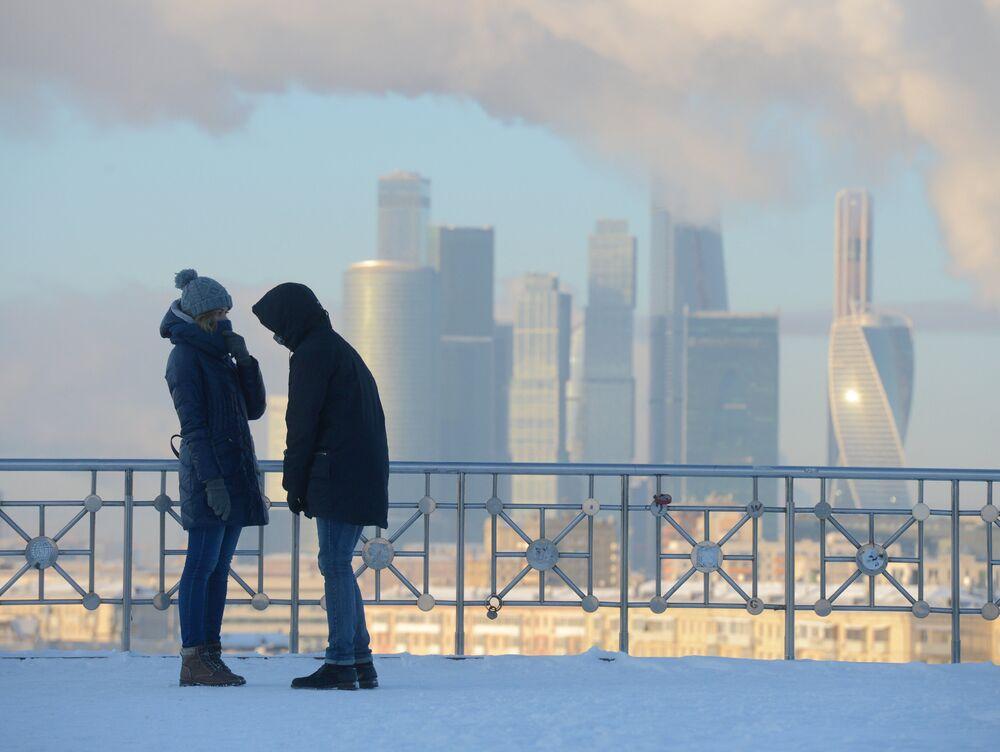 شخصان يقفان على خلفية ناطحات سحاب لـ موسكو سيتي، ودرجة الحرارة 27 تحت الصفر.