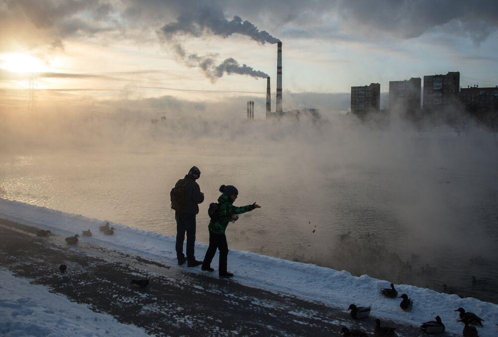 أشخاص يقفون على ضفة بحيرة كوجوخوفسكي بموسكو ويطعمون طيور البط، ودرجة الحرارة 24 تحت الصفر