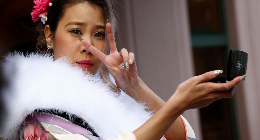 فتاة يابانية ترتدي الزي التقليدي الياباني كيمونو تمسك بمرأتها وتعدّل على المكياج، اليابان 9 يناير/ كانون الثاني 2017