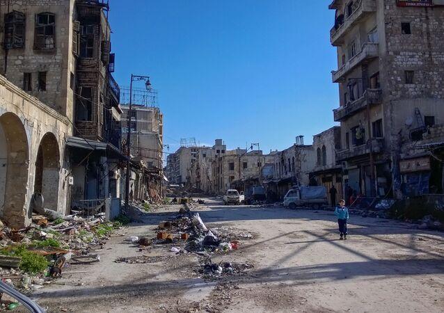 صبي يسير في شارع بحي الناظرية في حلب، سوريا