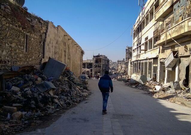 رجل يسير في شارع بحي الناظرية في حلب، سوريا