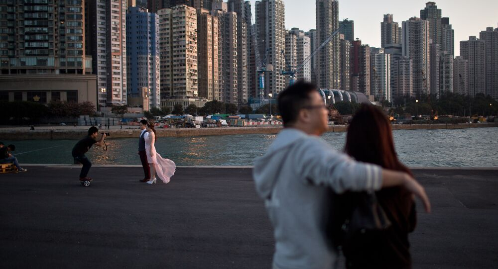 A couple (L) pose for their pre-wedding photographs on a public pier in Hong Kong on November 28, 2015