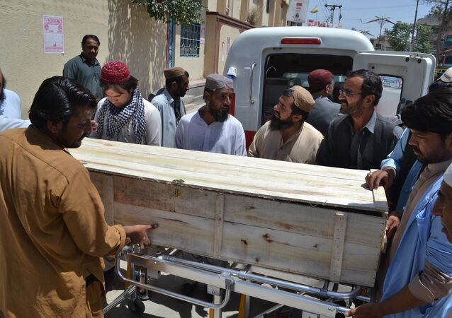 People stand near a coffin carrying a body one of the victims in a reportedly US drone strike in the Ahmad Wal area in Baluchistan province of Pakistan, at a local hospital in Quetta, Pakistan, Sunday, May 22, 2016.