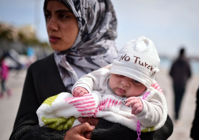 A Syrian refugee holds a two-month old baby as refugees and migrants who broke out from Chios detention camp, and camped out in the port of the city, stage a protest with their children chanting 'No Turkey' on April 3, 2016.