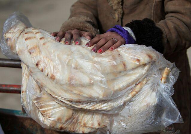 امرأة تحمل خبزاً في حلب، سوريا 30 يناير/ كانون الثاني 2017