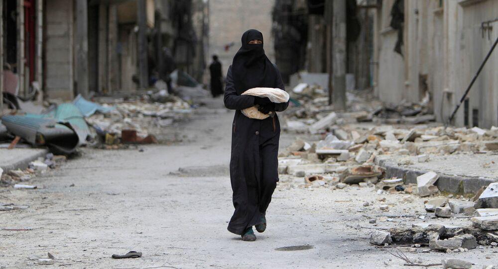 امرأة تحمل خبزاً في أحد شوارع حلب، سوريا 30 يناير/ كانون الثاني 2017