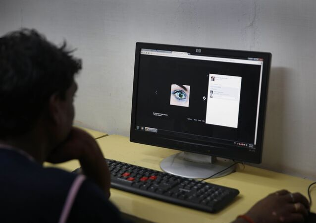 An Indian youth uses the internet at a cyber cafe in Allahabad, India.