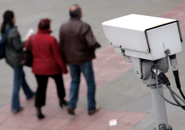 A police CCTV camera observes people walking in the Embankment area of central London