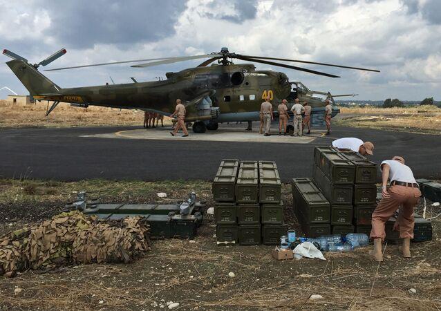 فريق من المهندسين التقنيين بجوار المروحية مي-24 في قاعدة المطار العسكري السوري حميميم في اللاذقية بسوريا