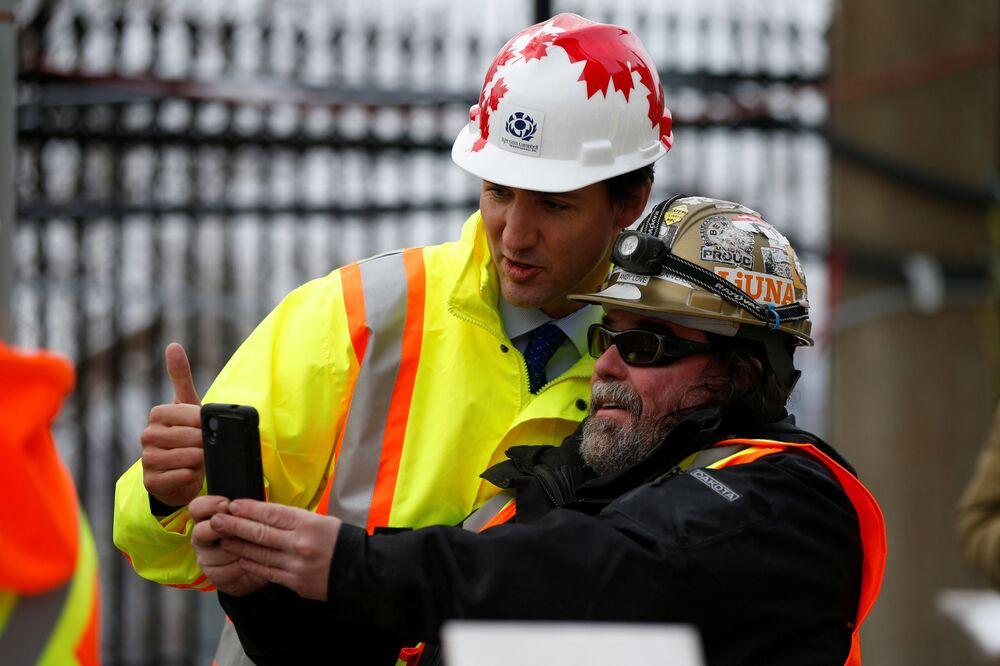 رئيس وزراء كندا جاستن ترودو يلتقط صورة سيلفي مع عامل بناء