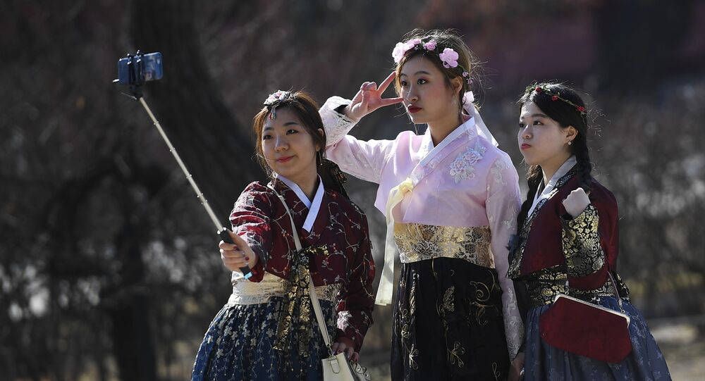 فتيات في سيؤول في زي تقليدي تلتقطن صور سيلفي من أمام قصر تشانغدوك في كوريا الجنوبية