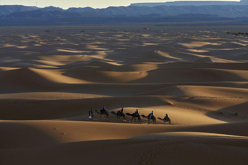 مرشد السياح يرافق قافلة من الجمال يركبها السياح في المرزوقة على طول طريق ألف قلعة في جبال الأطلس، المغرب 5 مارس/ آذار 2017