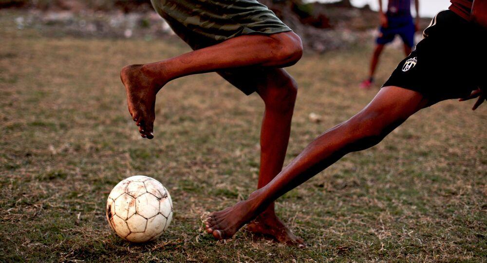 كوبيون يلعبون كرة القدم في ملعب للكرة بمدينة باراكوا، كوبا