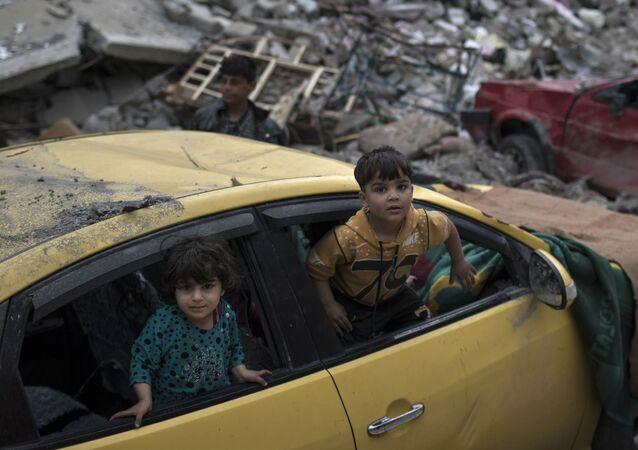 أطفال يلعبون داخل سيارة دمرت خلال المواجهات الحامية التي دارت بين قوات الأمن العراقية وتنظيم داعش في الجانب الغربي من الموصل، العراق 1 أبريل/ نيسان 2017