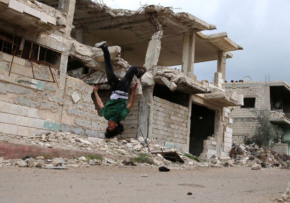الباركور الحربي السوري - إبراهيم القديري (19 عاماً، ومهند القديري (18 عاماً) يستعرضان مهارتهما بين ركام المباني في مدينة  إنخل غرب الدرعة، سوريا 7 أبريل/ نيسان 2017