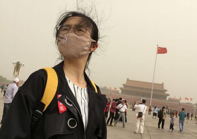 فتاة تزور ساحة تيانامين بينما تضرب عاصفة  رملية (غبار) في بكين، الصين 4 مايو/ آيار 2017