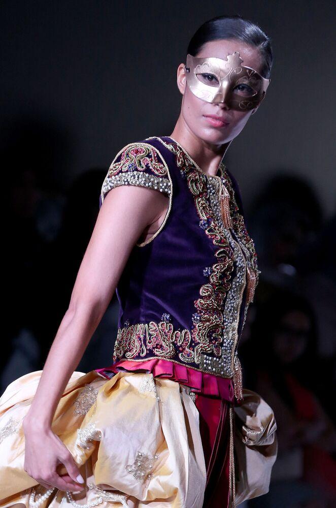 عارضة أزياء تقدّم فستانا من تصميم المغربية فايزة عنتري بوزار خلال عرض الأسبوع في الكويت، 8 مايو/ آيار 2017