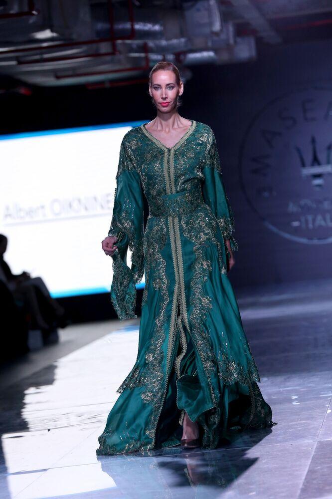 Альт: عارضة أزياء تقدّم زياً من تصميم المغربي ألبرت واكنين خلال عرض أسبوع الموضة في الكويت، 7 مايو/ آيار 2017