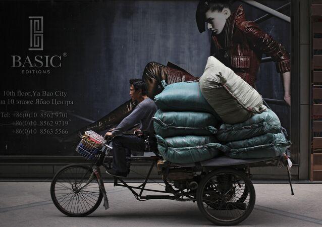 رجل يركب دراجة هوائية على خلفية إعلان للمركز التجاري ريتان الدولي في بكين، الصين 8 مايو/ آيار 2017