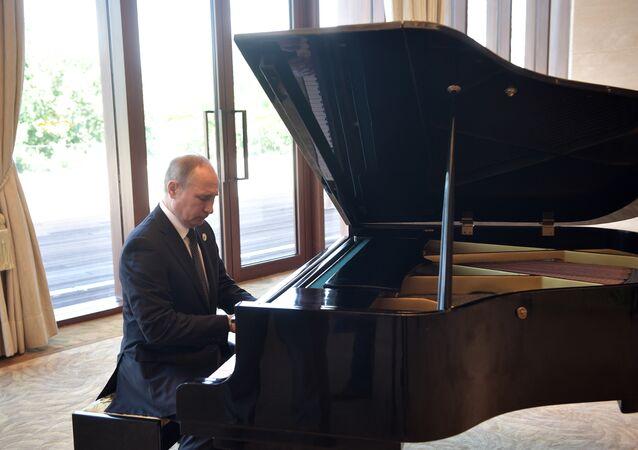 فلاديمير بوتين يعزف على البيانو قبل لقائه الرئيس الصيني
