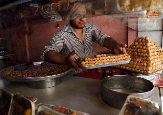 رجل يحضر الحلويات في مدينة الدوما، سوريا