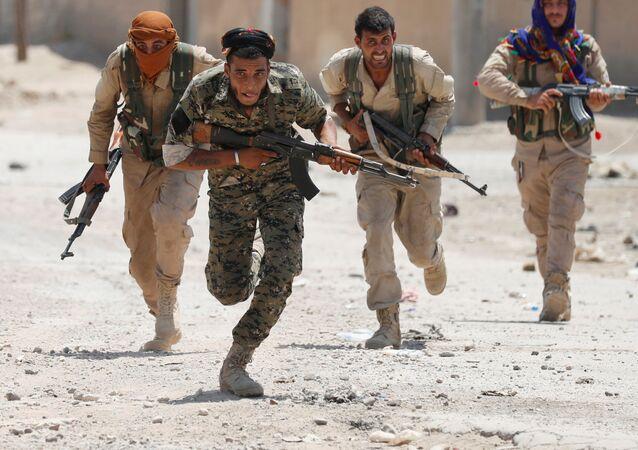 مقاتلون أكراد من وحدات حماية الشعب يجرون في إحدى شوارع مدينة الرقة، سوريا 3 يوليو / تموز 2017.
