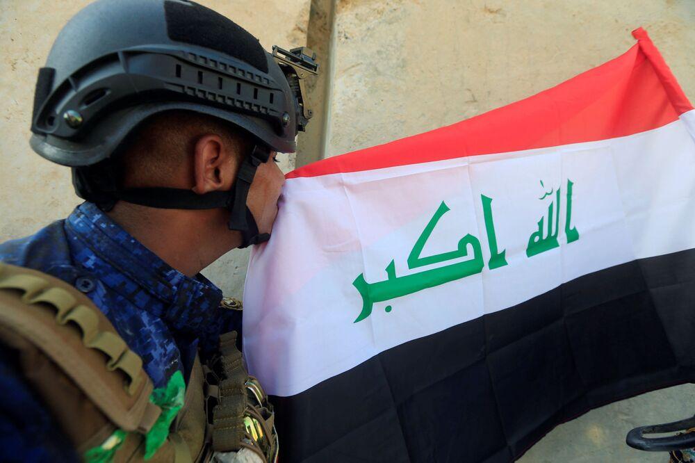 أحد عناصر الشرطة العراقية يقبل العلم العراقي بعد تحرير الموصل العراقية 9  يوليو/ تموز 2017