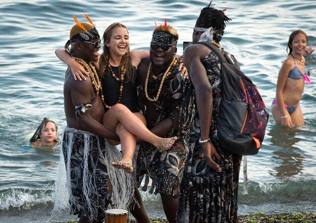 السياحة في القرم - فتاة أثناء التصوير مع سياح أجانب على شاطئ سوداكو