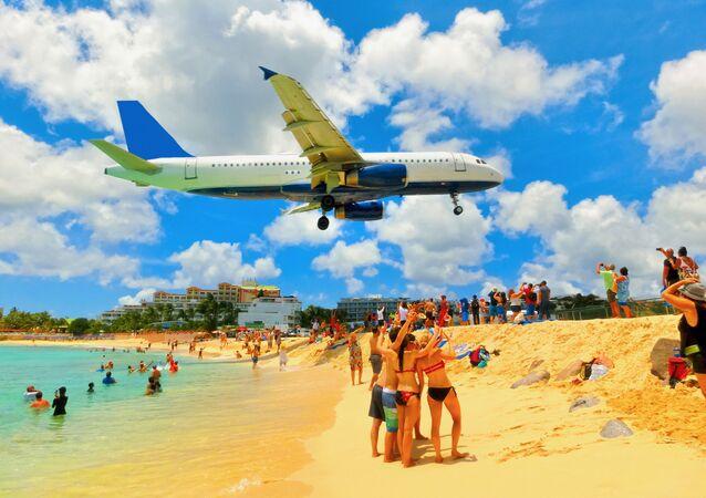 طائرة تحلق فوق شاطئ البحر، قبيل هبوطها في مطار الأميرة جوليانا في جزيرة سان مارتين