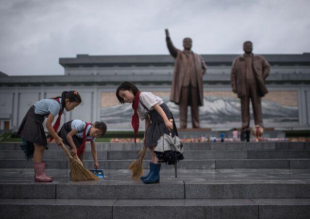 تلاميذ ينظفون الدرج الذي يقود إلى تماثيلي الزعيمين الكوريين الشماليين الراحلين كيم إيل سونغ وكيم جونغ إيل، على تلة مانسو حيث تصادف البلاد يوم النصر فى بيونغ يانغ، كوريا الشمالية فى 27 يوليو/ تموز 2017