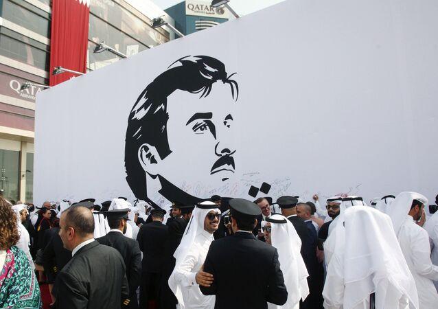 قطريون يتحمعون أمام صورة مجسمة لأمير قطر