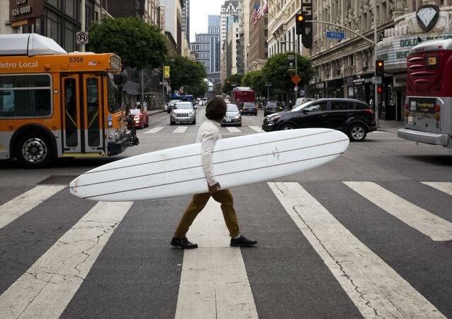 رجل يعبر الشارع حاملا لوح لركوب الأمواج في مدينة لوس أنجلوس، الولايت المتحدة 2 أغسطس/ آب 2017