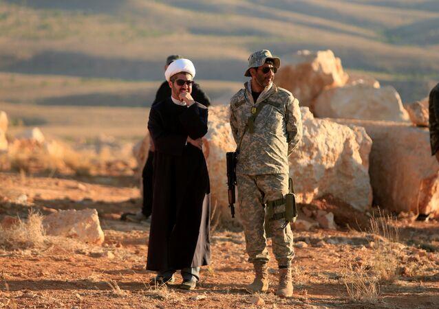شيخ يقف إلى جوار جندي من حزب الله في جرود عرسال