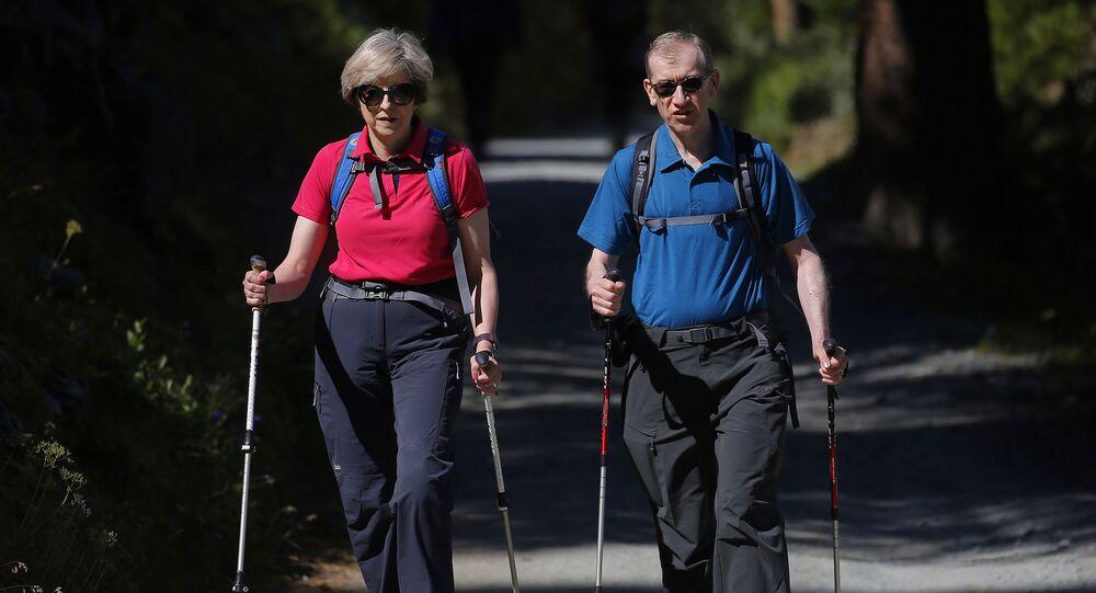 رئيسة وزراء البريطانية تيريزا ماي تمارس رياضة المشي مع زوجها