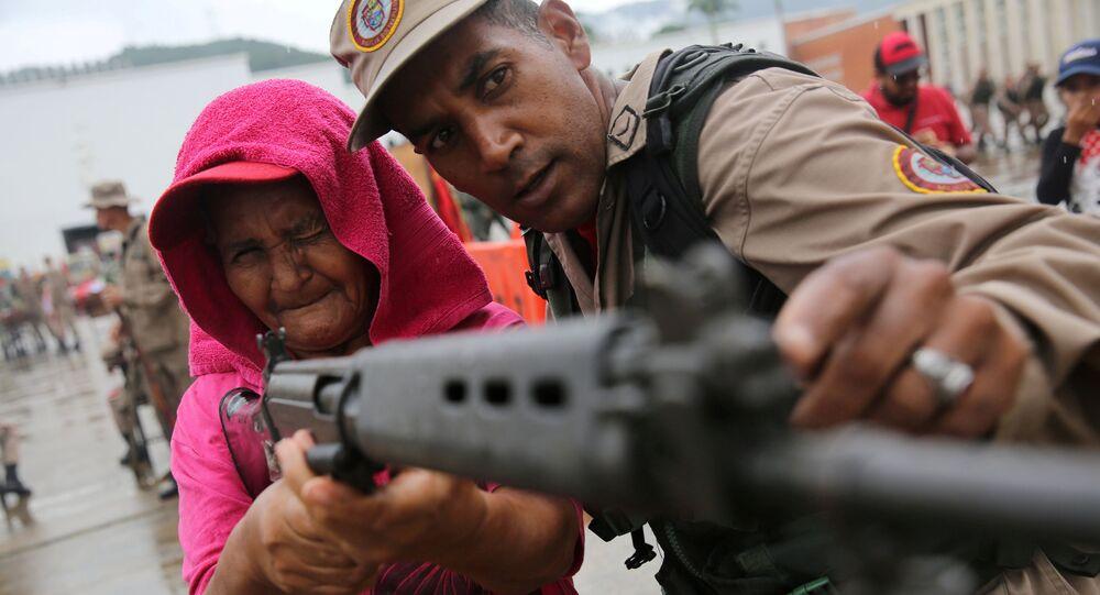 أحد أفراد قوات الشرطة الوطنية يدرب امرأة على حمل البندقية خلال تدريبات عسكرية في كاراكاس، فنزويلا 26 أغسطس/ آب 2017